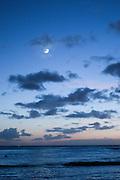 The moon over the ocean at dusk in Hawaii.