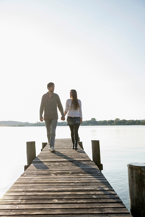 Young couple walking on wooden jetty