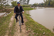 Rice farmer Nguyen Van Theo cycles through the rice fields near his home in Tho Quang Village, Vietnam. (Nguyen Van Theo is featured in the book What I Eat: Around the World in 80 Diets.) MODEL RELEASED.