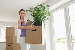 Woman carrying boxes new home moving in