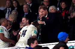 Prince Harry hands over a medal to England's Marland Yarde after the Autumn International match at Twickenham Stadium, London.