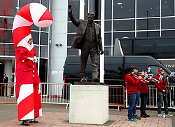 A festively dressed stilt walker stands beside the statue of Ted Bates outside the stadium during the Premier League match at St Mary's, Southampton.