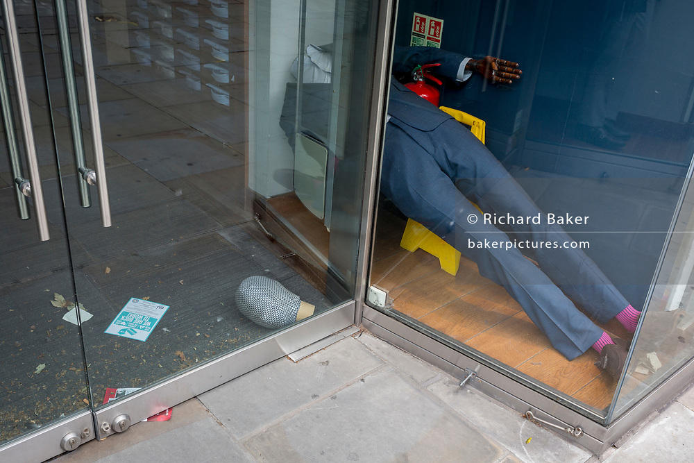 "After months of a menswear retailer's forced closure during the UK Coronavirus pandemc lockdown, one of its mannequins has fallen over on to the shop floor, its head lying by the door. The number of deaths from Coronavirus in the last 24hrs has increased by 287 to 37,979 while the government lowered the national Covid-19 alert level from 4 to 3, meaning the virus is considered to be ""in general circulation .. with ""a gradual reduction in restrictions"", on 19th June 2020, in the City of London, England."