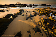 Huge reefs pierce the sands of the vast surfing beaches of Cordoama in South West Portugal.