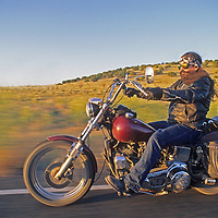 Mike Petti (MR) rides his motorcycle on a desert road near Cerritos, New Mexico.