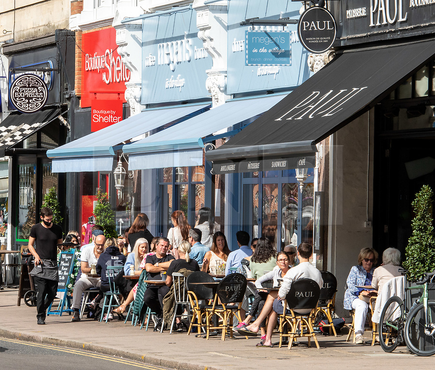 """© Licensed to London News Pictures. 12/09/2020. Surrey, UK. Groups of people enjoy a coffee and cake in the sunshine in Wimbledon Village in South West London this afternoon before the """"Rule of 6"""" comes into force on Monday as weather experts announce a 6 day mini heatwave in the South East of England this week with highs in excess of 29c. Prime Minister Boris Johnson is already under pressure after he announced on Friday that gatherings of more than six people will be banned from Monday in the hope of reducing the coronavirus R number. The Rule of Six as it is known, has already become unpopular with MPs and large families. Photo credit: Alex Lentati/LNP"""