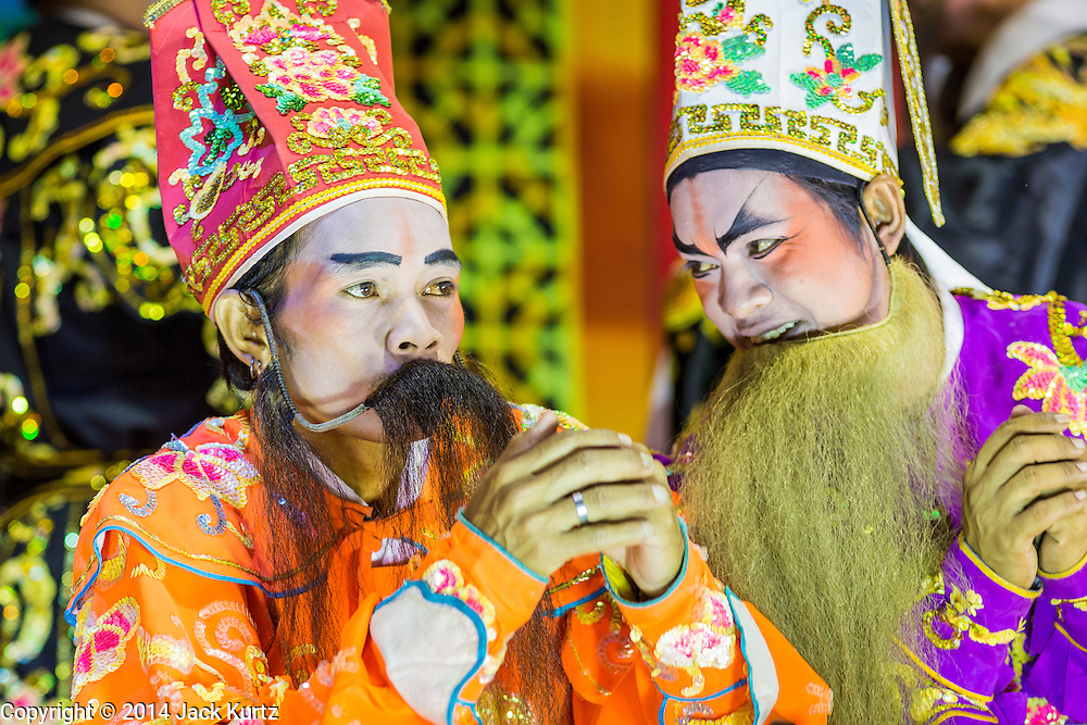 """19 AUGUST 2014 - BANGKOK, THAILAND:  Members of the Lehigh Leng Kaitoung Opera troupe perform at a Chaomae Thapthim Shrine, a small Chinese shrine in a working class neighborhood of Bangkok. The performance was for Ghost Month. Chinese opera was once very popular in Thailand, where it is called """"Ngiew."""" It is usually performed in the Teochew language. Millions of Chinese emigrated to Thailand (then Siam) in the 18th and 19th centuries and brought their culture with them. Recently the popularity of ngiew has faded as people turn to performances of opera on DVD or movies. There are still as many 30 Chinese opera troupes left in Bangkok and its environs. They are especially busy during Chinese New Year and Chinese holiday when they travel from Chinese temple to Chinese temple performing on stages they put up in streets near the temple, sometimes sleeping on hammocks they sling under their stage. Most of the Chinese operas from Bangkok travel to Malaysia for Ghost Month, leaving just a few to perform in Bangkok.        PHOTO BY JACK KURTZ"""