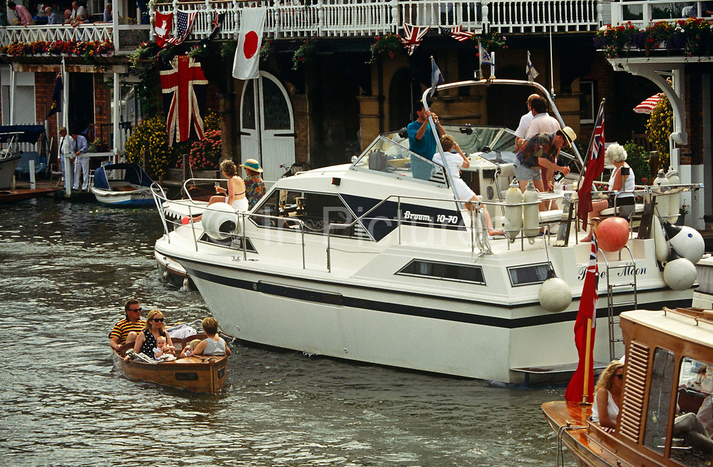 A family risk their safety near a larger cruiser while passing-by in a tiny motorised boat on the River Thames during the Henley Royal Regatta boat races, England. The father and children float past the larger vessel that could badly damage their boat in a collision. The river is busy on Regatta weekend and vessels of all shapes and sizes occupy an otherwise narrow stretch of water in rural Oxfordshire. Parties and good-humour on-board the cruisers still means that river laws and good behaviour must be followed to avoid accidents. In 1829 a boat race challenge was held between teams representing the universities of Oxford and Cambridge. The venue chosen was a straight stretch of the Thames at the small town of Henley-on-Thames. Now held July and is one of the main dates on the sporting calendar and social season for the hoi polloi.