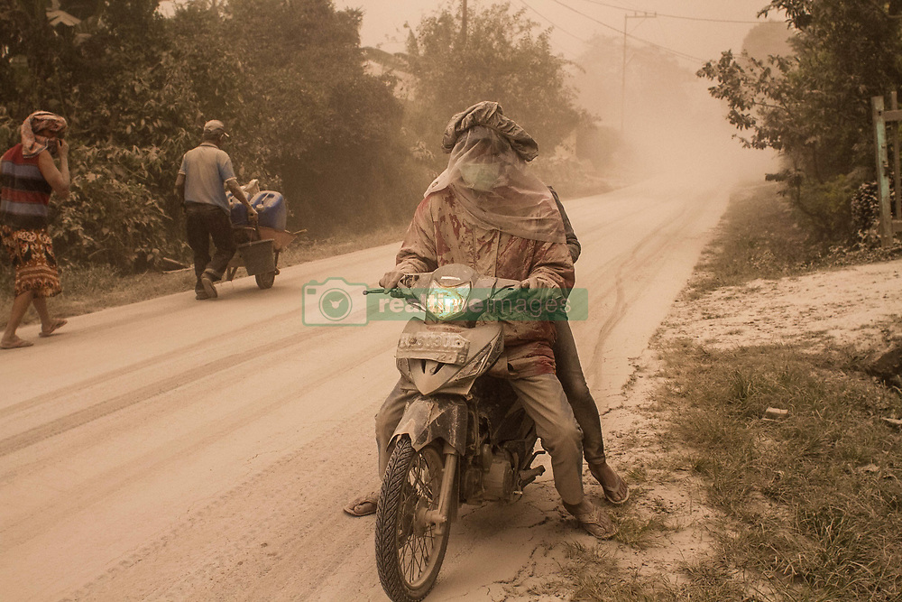 August 3, 2017 - Karo, North Sumatra, Indonesia - Local residents covered in volcanic thick dust on their motorbikes when the eruption of Sinabung released pyroclastic flows into the air, in Karo. The volcano destroys volcanic ash as high as 4.2 kilometers (2.2 miles), one of its biggest eruptions. In recent months high activity. (Credit Image: © Ivan Damanik via ZUMA Wire)
