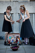 Two female puppeteers operate their puppet show on the Southbank. The puppets perform in a garage rock band to guitar music.