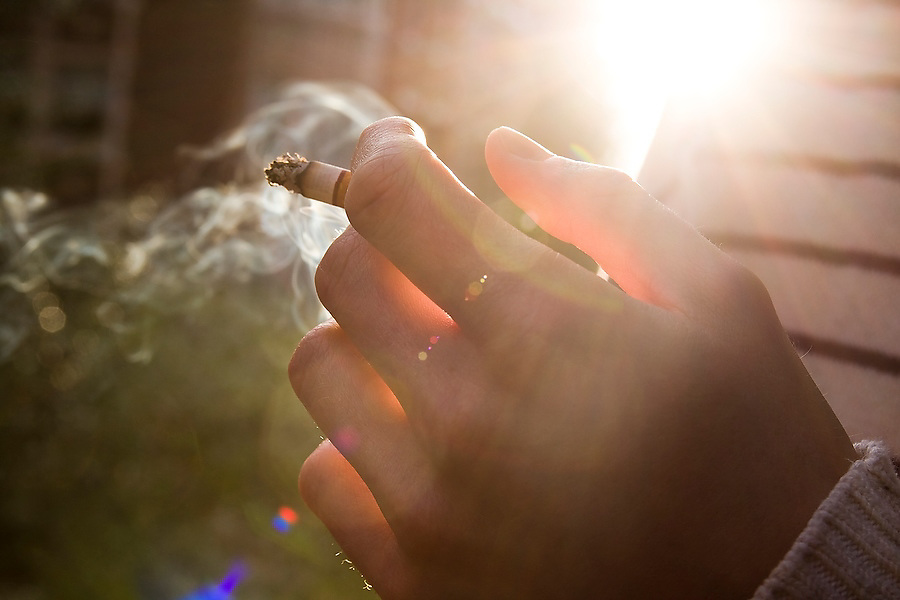 A young man holds a lit cigarette in his hand outdoors at sunset.