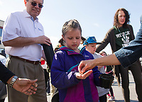 Julie Westcott hands Austyn McCullough two pumpkin seeds to plant during the 2017 Pumpkin Fest kickoff event at the Bank of NH parking lot on Thursday morning.  (Karen Bobotas/for the Laconia Daily Sun)