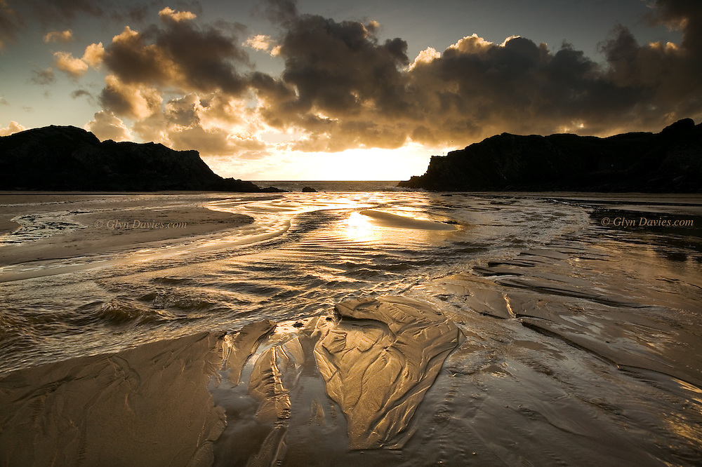 Sunset after rain at Porth Dafarch, a narrow cove with a sandy beach, very popular with tourists. As the tide retreats numerous streams from surrounding coutryside cut their way through the soft sands.
