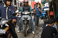 A woman breathes through a piece of fabric in the heavy Jakarta traffic Pollution and bad air quality defines Jakarta today. 2009 <br /> Une femme respire au travers d'un masque de tissus au milieu de la circulation de motos. Pollution et embouteillages caractérisent Jakarta aujourd'hui. 2009 2009