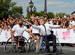 French President Emmanuel Macron returns the ball while sitting in a wheelchair as he plays tennis on the Pont Alexandre III in Paris, France, June 24, 2017. The French capital is transformed into a giant Olympic park to celebrate International Olympic Days with a variety of sporting events for the public across the city during two days as the city bids to host the 2024 Olympic and Paralympic Games. Photo by Jean-Paul Pelissier/Pool/ABACAPRESS.COM