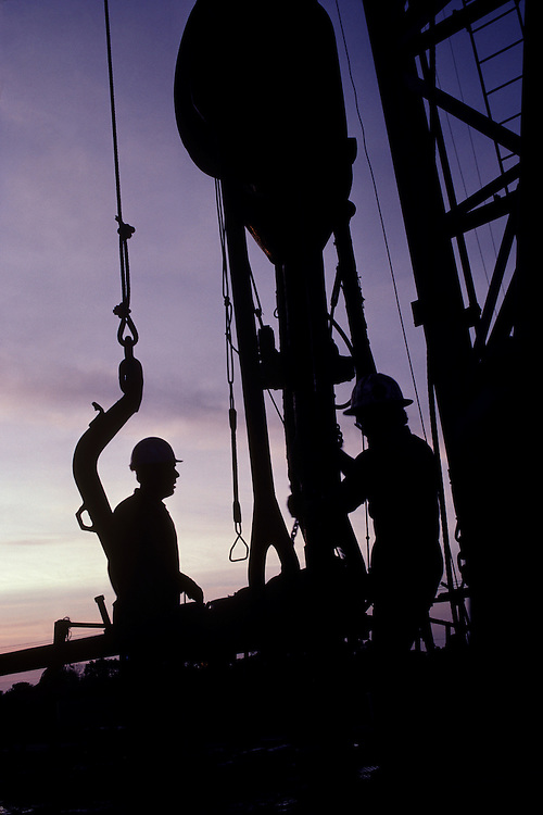 Silhouette of oil rig workers against purple sky at dusk, Webster, Texas.