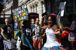"""© Licensed to London News Pictures . 28/08/2021. Manchester, UK. Rainbow Noir demonstrators dance and carry a placard reading """" Elevate and celebrate LGBTQI people of colour """" . People take part in a Reclaim Pride march through Manchester City Centre , in opposition to the management of the city's """"official"""" Manchester Pride charity festival . The Manchester Pride charity parade was cancelled in 2020 due to Coronavirus . An """"equality march"""" organised by Manchester Pride charity was due to take place on Deansgate as the protest passed through the Gay Village . Protesters object to Manchester Pride charity's withdrawal of funding for the LGBT Foundation's condom distribution scheme and HIV charity George House Trust as well as increasing commercialisation of the annual event . Photo credit: Joel Goodman/LNP"""