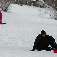 Children enjoy playing in the snow in Budapest, Hungary on January 19, 2013. ATTILA VOLGYI