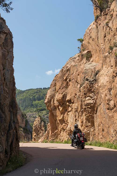 View of motorcycle on road on rocky cliff, Calanches de Piana, Corsica, France