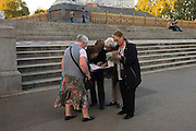 Five women consult a map of London, trying to find a landmark in the capital city, beneath the Albert Memorial.