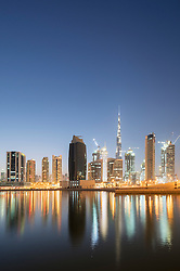 Skyline of towers reflected in the Creek at dusk in Business Bay  in Dubai United Arab Emirates