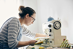 February 15, 2018 - Woman using electric sewing machine to make curtains (Credit Image: © Mint Images via ZUMA Wire)