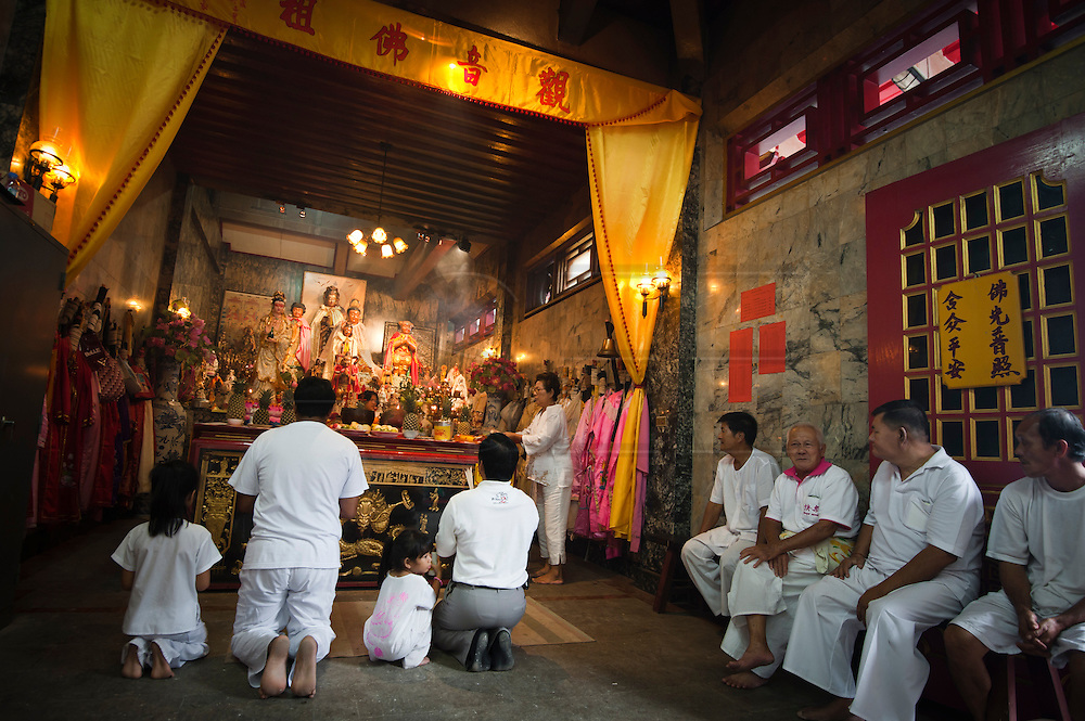 Locals praying inside a shrine during the Vegetarian Festival in Phuket, Thailand. Every year during the ninth lunar month of the Chinese calendar, the Phuket Vegetarian Festival kicks off. The religious festival in Phuket, Thailand, lasts for 10 days, during which sacred rituals take place in the many Chinese shrines and temples. Walking on fire and climbing ladders with bladed rungs barefoot are two of several rituals believed to bring good fortune. The main purpose of the festival, however, is spiritual cleansing and merit-making. The origins of the festival date back to 1825, when a traveling Chinese opera company came to Phuket to perform for the miners there. An epidemic broke out and as the members of the company fell sick, they adhered to a vegetarian diet to honor two of the Emperor Gods, Kiew Ong Tai The and Yok Ong Sone Teh. When they became well again shortly thereafter, the people of Phuket followed the companyÕs example - and have celebrated the festival ever since to bring good luck to their communities.