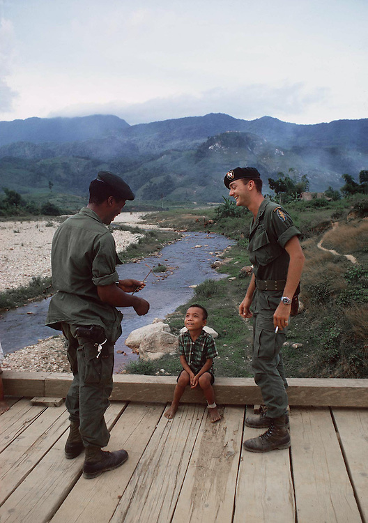 American Special Forces soldier chats with a soldier of the South Vietnamese army and a local boy during a visit to a village in the Central Highlands, Vietnam, October 1969. Photographed by Terry Fincher