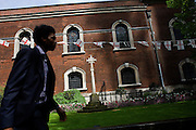 City worker passes-by on St George's Day as flags fly during the lunchtime of 23rd April, England's national day. Christian worship has probably been offered at the church of St. Botolph's without Bishopsgate since Roman times. The original Saxon church, the foundations of which were discovered when the present church was erected, is first mentioned as 'Sancti Botolfi Extra Bishopesgate' in 1212.St. Botolph without Bishopsgate may have survived the Great Fire of London unscathed, and only lost one window in the Second World War, but on 24 April 1993 was one of the many buildings to be damaged by an IRA bomb. The memorial cross (1916) at the garden's entrance is believed to be the first memorial of the Great War to be set up in England.