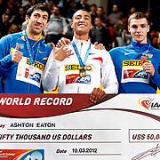 Gold medal winner Ashton Eaton (C) from the United States is flanked by silver medal winner Oleksiy Kasyanov from Ukraine, left, and bronze medalist Artem Lukyanenko from Russia as he holds a cheque he got for setting a new indoor World Record during the IAAF World Indoor Championships at the Atakoy Athletics Arena, Istanbul, Turkey. Photo by TURKPIX