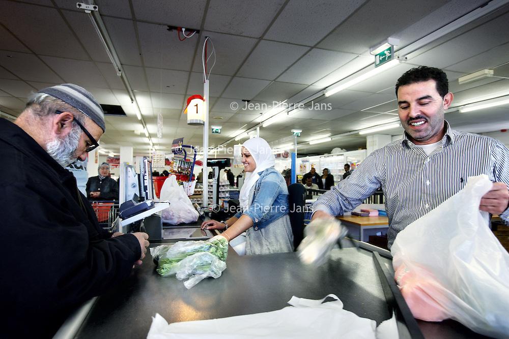 Nederland, Amsterdam , 3 mei 2011..Supermarkt Tanger..De etnische supermarkt Tanger in Slotermeer is met die prijs goedkoper dan de winkels in het Marokkaanse Tanger. De winkel trekt klanten aan van ver buiten de stad..Op de foto de Marokkaanse eigenaar Ahmed Barghaoul helpt mee met boodschappen inpakken...Foto:Jean-Pierre Jans