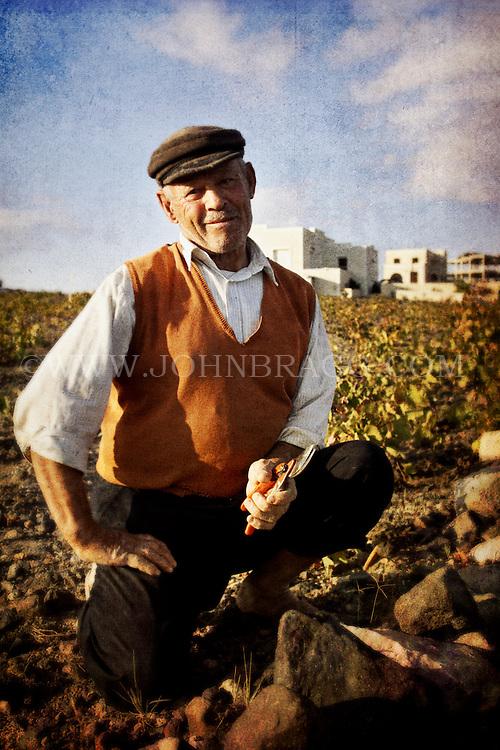 A man and his vineyard, Santorini, Greece.