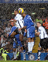 Photo: Ed Godden.<br />Chelsea v Fulham. The Barclays Premiership. 30/12/2006.<br />Chelsea's Ashley Cole (R), is challenged in the air by Collins John as the rain pours down.
