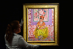"""© Licensed to London News Pictures. 15/06/2017. London, UK. A staff member hangs """"La Martiniquaise"""", 1931, by Raoul Dufy (estimate GBP500-700k). Preview of Impressionist and Modern art sale, which will take place at Sotheby's New Bond Street on 21 June.  Photo credit : Stephen Chung/LNP"""