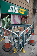 Hole in the pavement is cordoned off to be fixed with warning bariers outside Subway shop in Birmingham, United Kingdom.