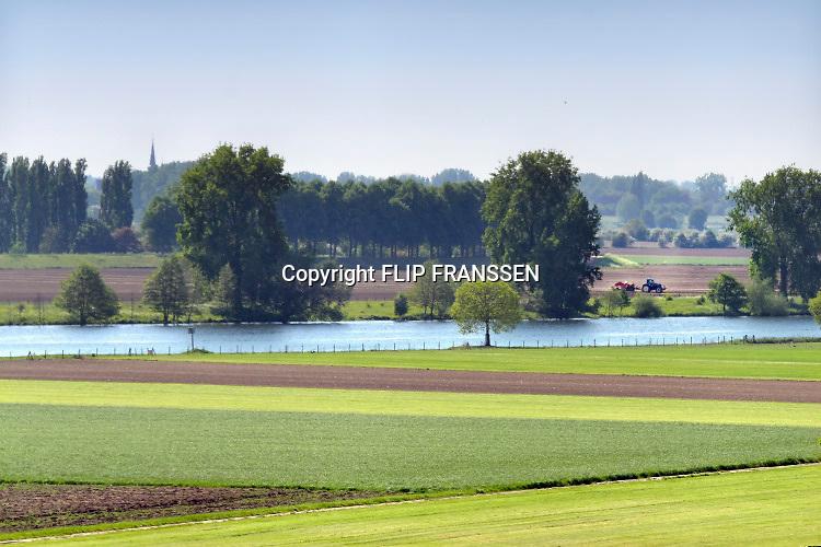 Nederland, Batenburg, Ravenstein, 8-5-2018 Bakenbomen langs de rivier de Maas gaan verdwijnen door het uitsterfbeleid van Rijkswaterstaat. Bij hoog water zijn de bomen een hulpmiddel voor navigatie, een baken voor de schippers. De Maasoevers moeten volgens RWS vrij zijn van obstakels en dus worden de bomen niet meer vervangen . Deze bakenbomen zijn karakteristiek voor het landschap langs de rivier de Maas . De Maas krijgt de ruimte. Door de aanleg van natuurvriendelijke oevers ontstaat er een geleidelijke overgang van water naar land. Op veel plaatsen langs de meanderende maas zijn nevengeulen aangelegd om het water meer ruimte tegeven . Foto: Flip Franssen