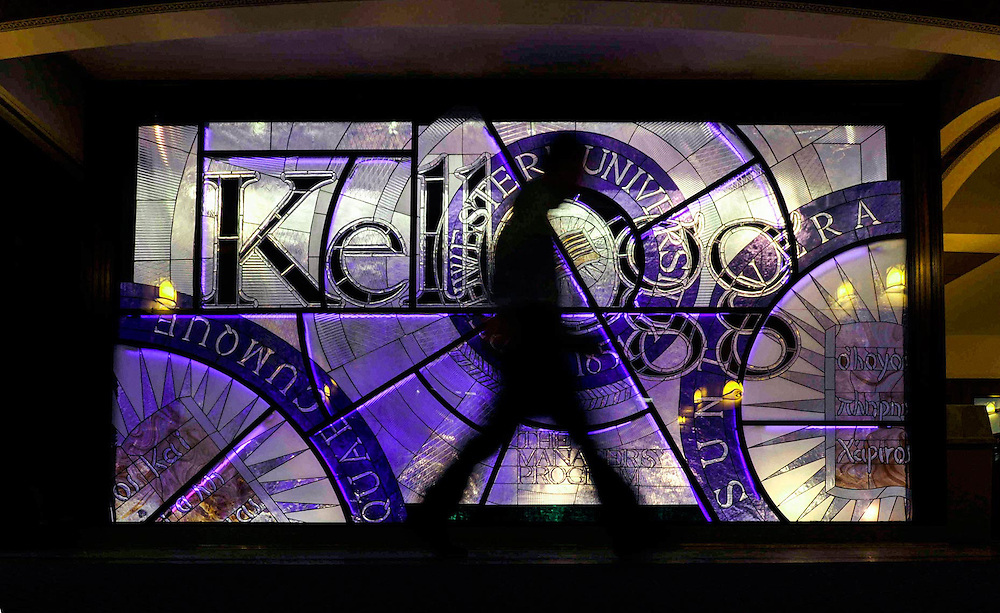 A student walks past a stained glass wall at the Chicago campus of the Kellogg School of Management .