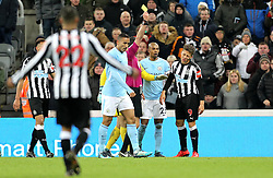 Newcastle United's Dwight Gayle (right) is booked for diving during the Premier League match at St James' Park, Newcastle.