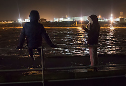 © Licensed to London News Pictures. 13/01/2017. Great Yarmouth, UK. People watch the River Yare at high water at Gorleston-on-Sea near Great Yarmouth. The Environment Agency has warned residents to prepare for evacuation as as they fear flooding at tonight's high tide. Photo credit: Peter Macdiarmid/LNP