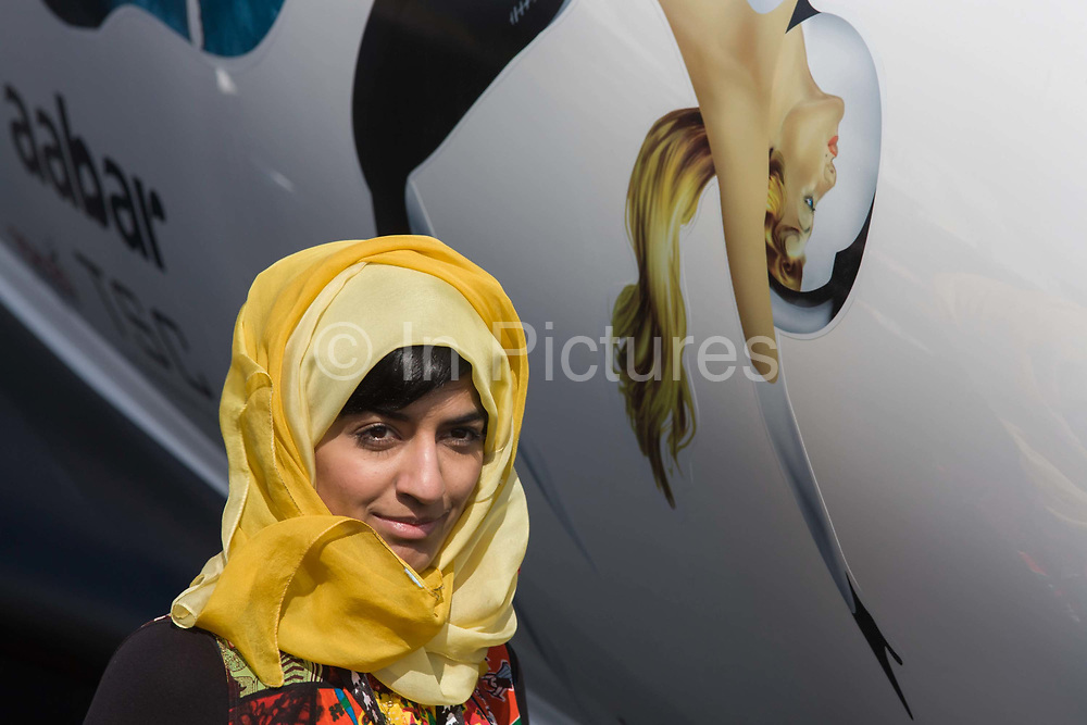 An Islamic lady stands for a photo next to the painted lady on the feselage of Virgin Galactic's space tourism spaceplane vehicle, SpaceShipTwo (SS2) at the Farnborough air show. SHowing a clash of cultures amid the latest in aviation and space technology, the woman stands looking the picture of modesty alongside the more sexual representation of a flying female of Virgin's brand identity. Virgin Galactic is one of the leading potential space tourism groups, is planning to begin passenger service aboard the VSS Enterprise, a Scaled Composites SpaceShipTwo type spacecraft.