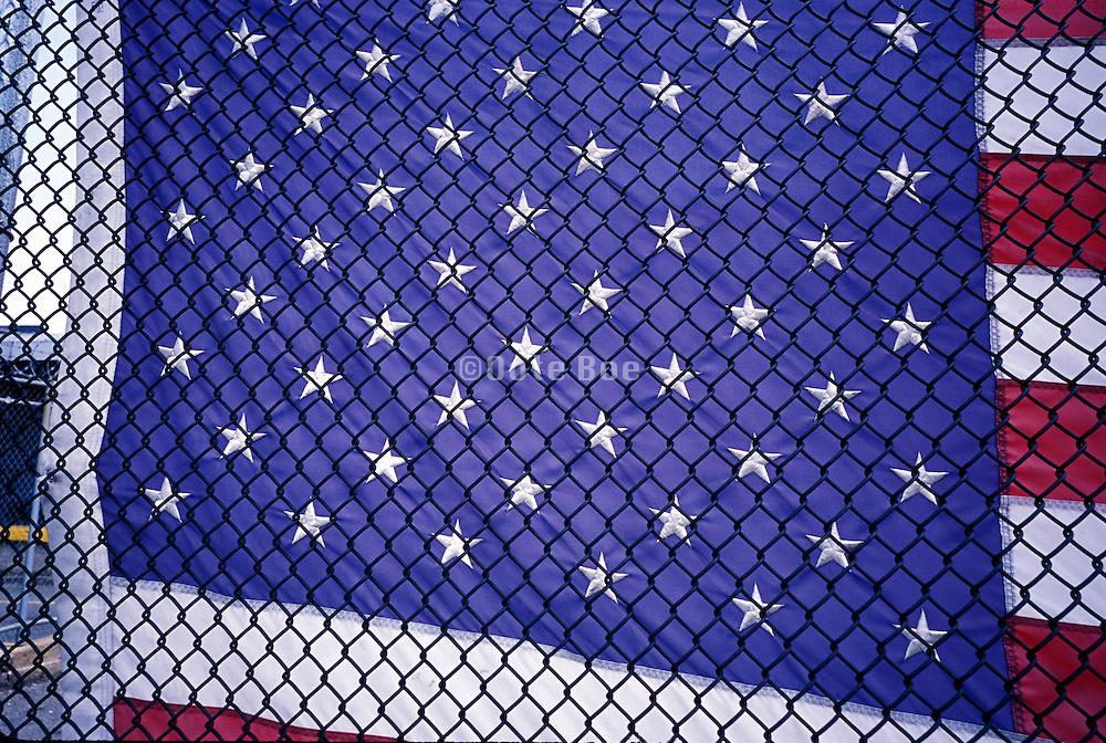Close up of a flag through a fence