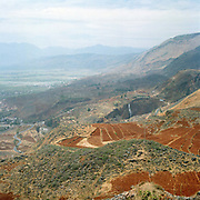 Landscape view looking towards a valley in the northern mountainous region of Yunnan province showing winding roads and fallow fields.