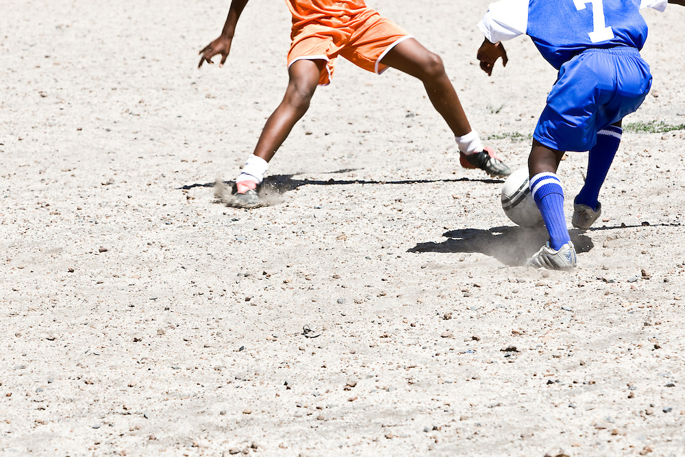 Boys from Imizamu Yethu informal settlement play soccer on a dirt pitch in Hout Bay, Cape Town, South Africa.