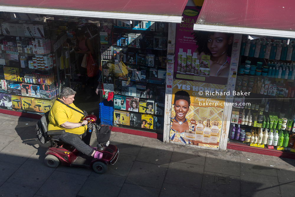 A disabled lady drives her mobility scotter past a beauty and womens' accessory shop on the Walworth Road, on 27th February 2019, in London, England.