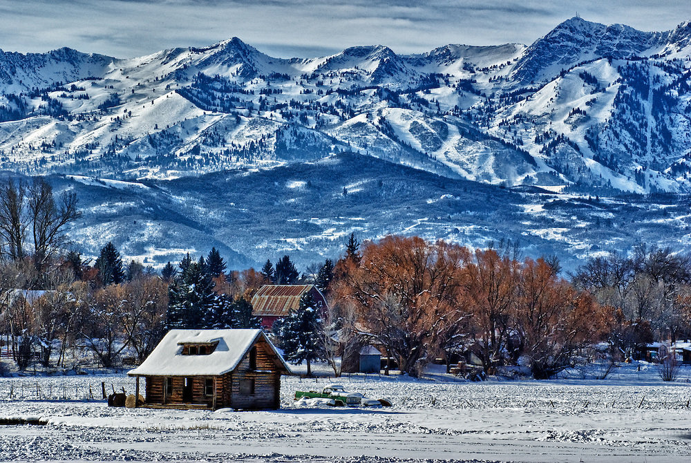 An old log cabin with Snowbasin Ski Resort in the background.