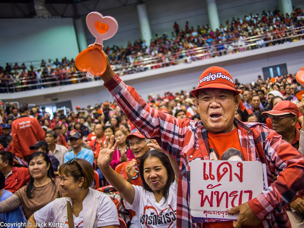 """23 FEBRUARY 2014 - NAKHON RATCHASIMA (KORAT), NAKHON RATCHASIMA, THAILAND: A man cheers for Red Shirt speakers in Korat. The United front of Democracy against Dictator (UDD or Red Shirts), which supports the elected government of Yingluck Shinawatra, staged the """"UDD's Sounding of the Battle Drums"""" rally in Nakhon Ratchasima (Korat) to counter the anti-government protests that have gripped Bangkok since November. Around 4,000 of UDD's regional and provincial coordinators along with the organization's core members met at Liptapunlop Hall inside His Majesty the King's 80th Birthday Anniversary Sports Complex in Korat to discuss the organization's objectives and tactics against anti-government protestors, which the UDD says """"seek to destroy the country's democracy."""" The UDD leadersa announced that they will march to Bangkok and demonstrate against anti-government protests led by Suthep Thaugsuban.   PHOTO BY JACK KURTZ"""