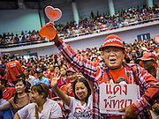 "23 FEBRUARY 2014 - NAKHON RATCHASIMA (KORAT), NAKHON RATCHASIMA, THAILAND: A man cheers for Red Shirt speakers in Korat. The United front of Democracy against Dictator (UDD or Red Shirts), which supports the elected government of Yingluck Shinawatra, staged the ""UDD's Sounding of the Battle Drums"" rally in Nakhon Ratchasima (Korat) to counter the anti-government protests that have gripped Bangkok since November. Around 4,000 of UDD's regional and provincial coordinators along with the organization's core members met at Liptapunlop Hall inside His Majesty the King's 80th Birthday Anniversary Sports Complex in Korat to discuss the organization's objectives and tactics against anti-government protestors, which the UDD says ""seek to destroy the country's democracy."" The UDD leadersa announced that they will march to Bangkok and demonstrate against anti-government protests led by Suthep Thaugsuban.   PHOTO BY JACK KURTZ"