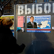 A female pedestrian in Tyumen looks at an election poster by a candidate of the United Russia party, which backs Russian President Vladimir Putin. The Siberian city enjoys a flush of cash from its oil and gas reserves.
