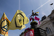 Flags and banners adorn the statue of Eros during a protest against climate change in the middle of Piccadilly Circus on 15th April, 2019 in London, United Kingdom.  Extinction Rebellion have blocked five central London landmarks in protest against government inaction on climate change. The youth group of Extinction Rebellion was based at Piccadilly Circus..