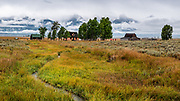 The Pink House, bunkhouse and barn preserved at John Moulton Homestead, at the corner of Mormon Row and Antelope Flats Road, in the valley of Jackson Hole, Grand Teton National Park, Wyoming, USA. This image was stitched from multiple overlapping photos.